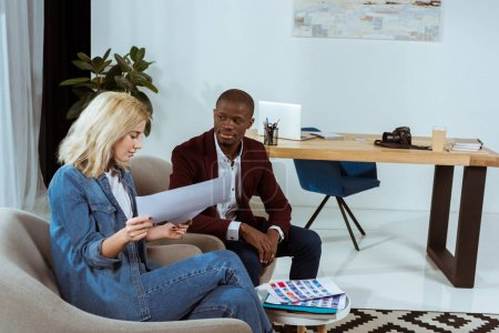interracial photographers choosing photos together while sitting in armchairs in office