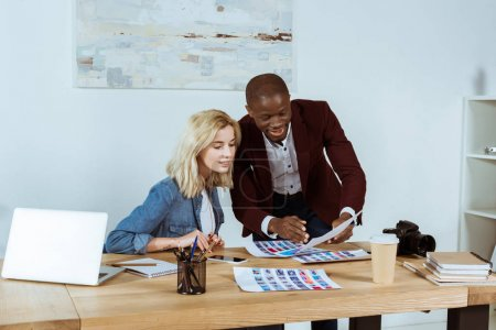 portrait of multiethnic photographers looking at portfolio at workplace in office