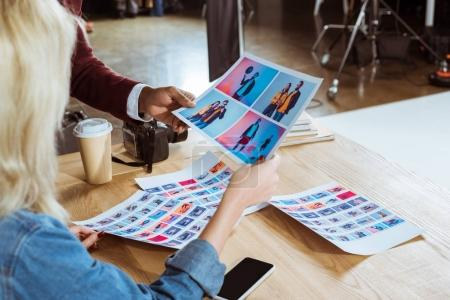 Photo for Cropped shot of multicultural photographers choosing photos together at workplace in office - Royalty Free Image