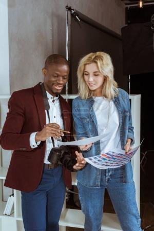portrait of smiling multiethnic photographers looking at portfolio together in studio