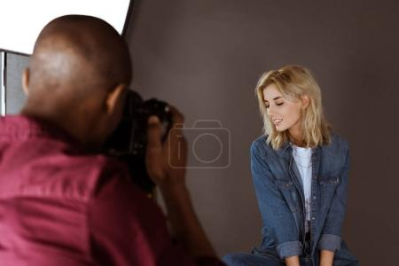 beautiful smiling caucasian woman posing while african american photographer taking picture in studio