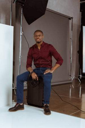 african american photographer with photo camera in hands looking at camera in studio