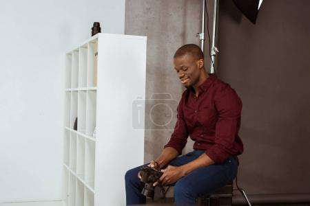 side view of smiling african american photographer looking at photo camera in hands while choosing photos in studio