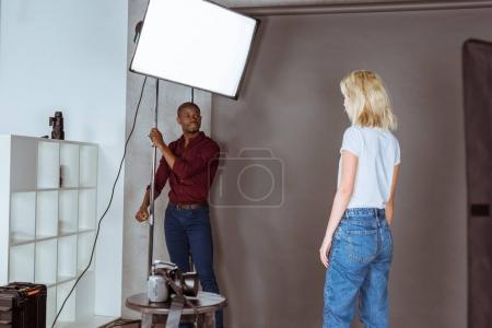 african american photographer correcting light before photoshoot in studio