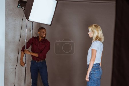 african american photographer correcting light before photoshoot in studio