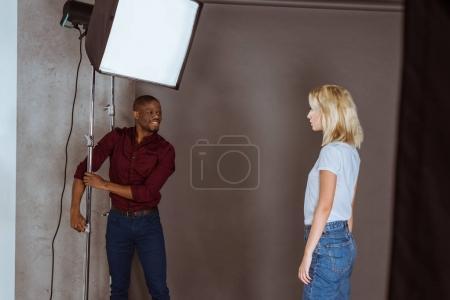 Foto de Fotógrafo americano africano corrección de luz antes de la sesión de fotos en estudio - Imagen libre de derechos