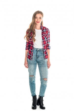 Photo for Full length view of beautiful young woman in checkered shirt and jeans looking at camera isolated on white - Royalty Free Image