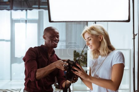 portrait of cheerful african american photographer and caucasian model choosing photos together during photoshoot in studio