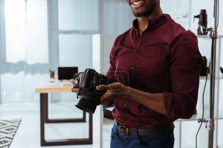 cropped shot of smiling african american photographer holding photo camera in hands in studio