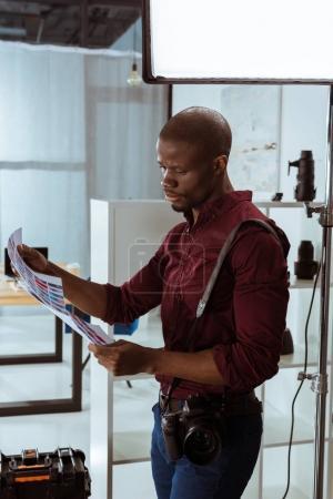 Foto de Vista lateral del fotógrafo americano africano con ejemplos de la sesión de fotos en manos de studio - Imagen libre de derechos