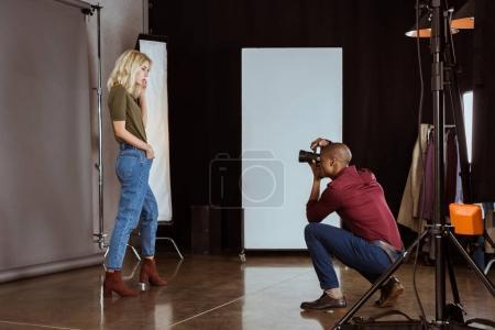 Photo pour Photographe afro-américain prenant une photo de modèle attrayant en studio - image libre de droit