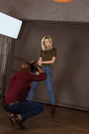 beautiful caucasian woman posing while african american photographer taking picture in studio