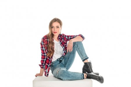Photo for Attractive young woman in checkered shirt and jeans sitting and looking at camera isolated on white - Royalty Free Image