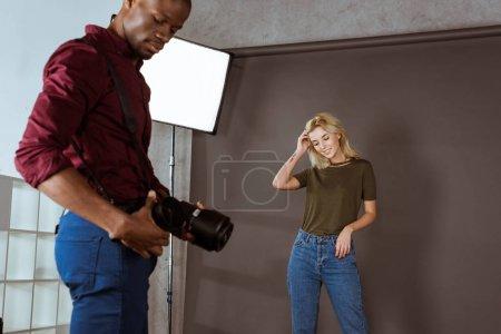 multiethnic photographer and model having photoshoot in studio