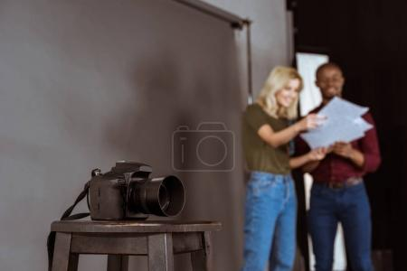 selective focus of photo camera and african american photographer and model looking at portfolio in studio