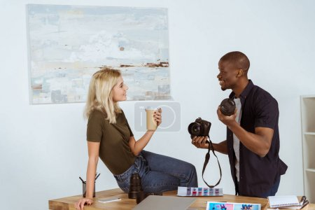 side view of interracial photographers having conversation at workplace in office