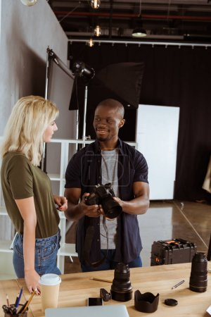 interracial photographers talking about photo cameras at workplace in studio