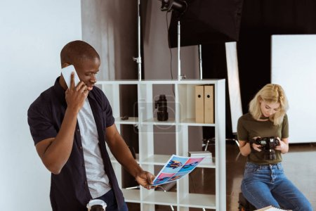 Photo for Afican american photographer talking on smartphone while caucaisan colleague choosing photos in studio - Royalty Free Image