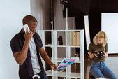 photographe américain Alfican parler sur smartphone et collègue caucaisan, choisir des photos en studio
