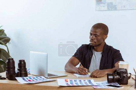 Photo pour Portrait de photographe afro-américaine concentré sur lieu de travail avec ordinateur portable au bureau - image libre de droit