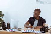 """Постер, картина, фотообои """"Портрет концентрированной афро-американский фотограф, работающий на рабочем месте с ноутбуком в офисе"""""""