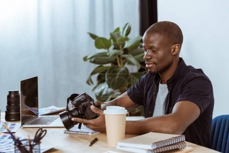 Photo for Portrait of african american photographer with photo camera at workplace with laptop in office - Royalty Free Image