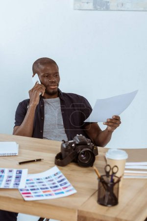 Photo for Portrait of concentrated african american photographer talking on smartphone while working in office - Royalty Free Image