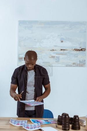Photo for Portrait of focused african american photographer looking at photoshoot examples in hands while standing at workplace - Royalty Free Image