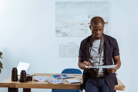 portrait of african american photographer looking at photoshoot examples in hands at workplace