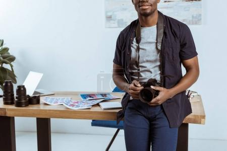 partial view of african american photographer with photo camera leaning on workplace in office