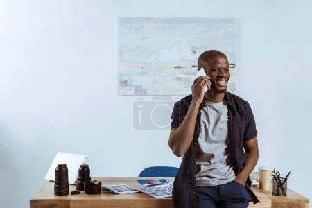 portrait of smiling african american photographer talking on smartphone at workplace in studio