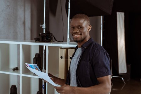 portrait of cheerful african american man with papers in hand looking at camera in studio
