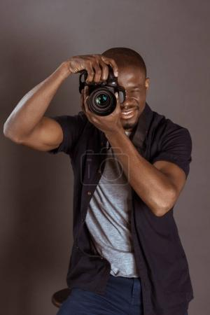 portrait of african american photographer taking picture on photo camera