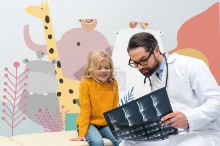 Photo pour Jeune beau pédiatre montrant le balayage de rayons X à la petite fille - image libre de droit