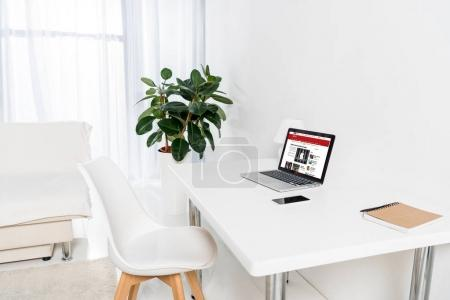 home office with laptop with bbc logo, smartphone and notebook on table