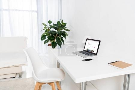 home office with laptop with airbnb logo, smartphone and notebook on table