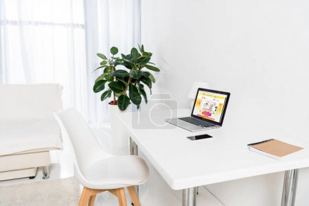 home office with laptop with aliexpress logo, smartphone and notebook on table