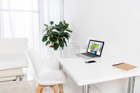 Photo pour Bureau à domicile avec ordinateur portable avec logo bbc, smartphone et ordinateur portable sur la table - image libre de droit