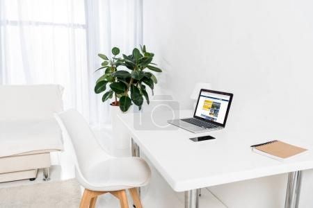 home office with laptop with bookingcom logo, smartphone and notebook on table