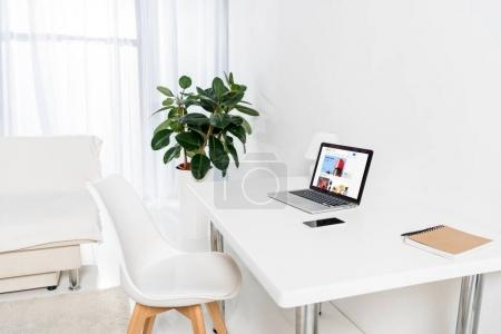 laptop with ebay logo, smartphone and notebook on table in living room