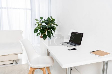 laptop with html code, smartphone and notebook on table in living room