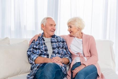 portrait of cheerful senior couple looking at each other while sitting on sofa