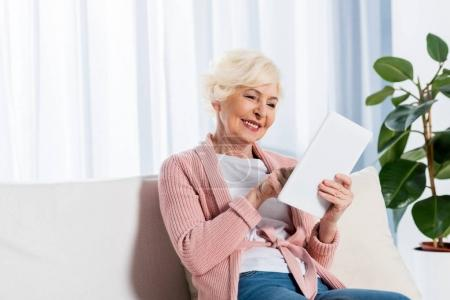 portrait of cheerful senior woman using digital tablet while sitting on sofa at home