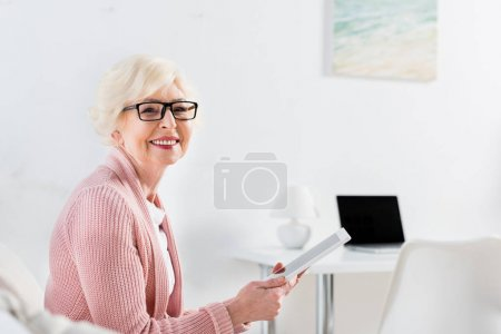 side view of smiling senior woman with tablet in hands resting on sofa and looking at camera at home
