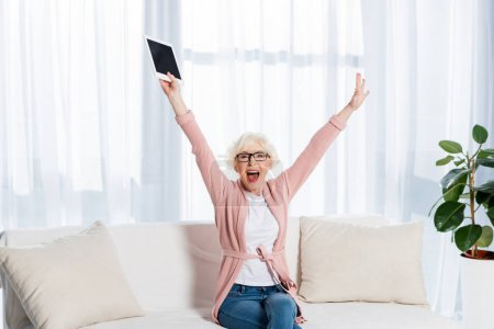 portrait of excited senior woman in eyeglasses with tablet in hand looking at camera at home