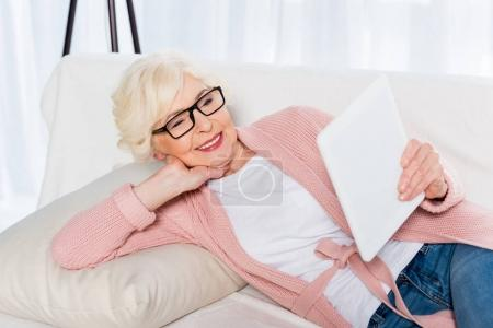 portrait of smiling senior woman in eyeglasses using tablet while resting on sofa at home
