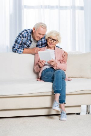 senior man hugging wife with digital tablet in hands on sofa at home