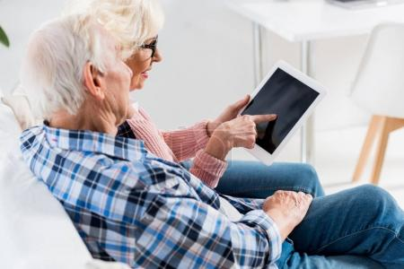 side view of senior couple using digital tablet with blank screen together
