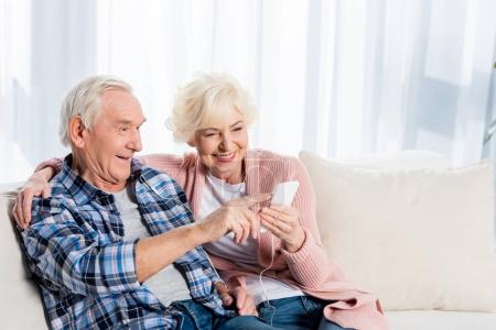 Photo for Happy senior couple in earphones listening music together at home - Royalty Free Image