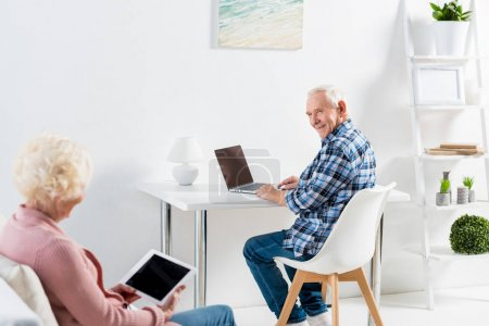 Photo for Partial view of senior man at table with laptop looking at wife sitting on sofa at home - Royalty Free Image